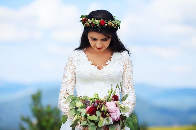 Een jong meisje in een krans in witte jurk.