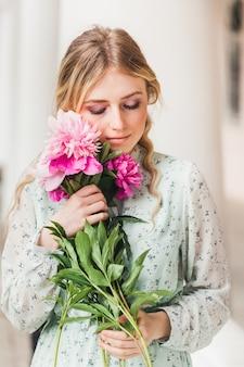 Een jong meisje in een lichte jurk in de zomer staat en houdt bloemen, pioenrozen, een boeket, een geschenk, een date, te wachten