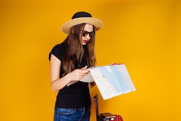Een jong meisje in een modieuze hoed en zonnebril onderzoekt een kaart, gaat op reis met een koffer