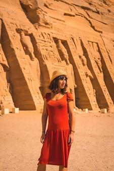 Een jong meisje in een rode jurk bezoekt de egyptische tempel van nefertari bij abu simbel in het zuiden van egypte in nubië naast het nassermeer. tempel van farao ramses ii, reislevensstijl