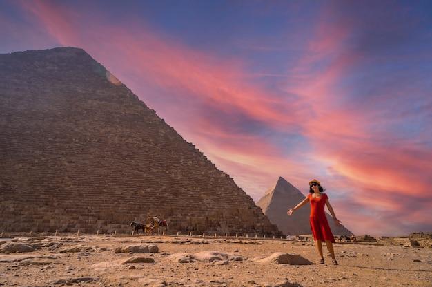 Een jong meisje in een rode jurk bij de piramide van cheops de grootste piramide bij zonsondergang. de piramides van gizeh zijn het oudste grafmonument ter wereld. in de stad caïro, egypte