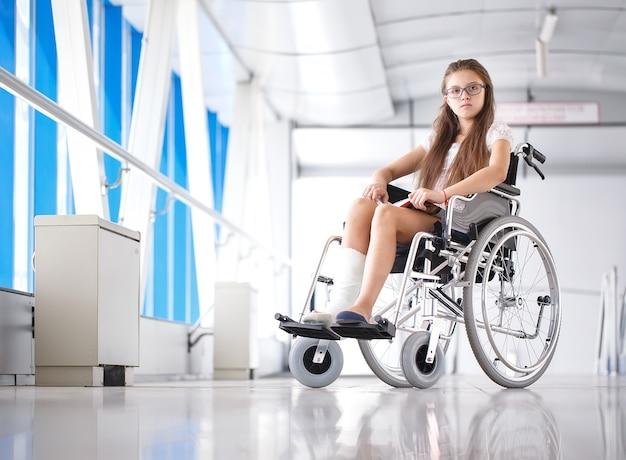 Een jong meisje in een rolstoel leest een boek, patiënt in een rolstoel in de gang van het ziekenhuis.