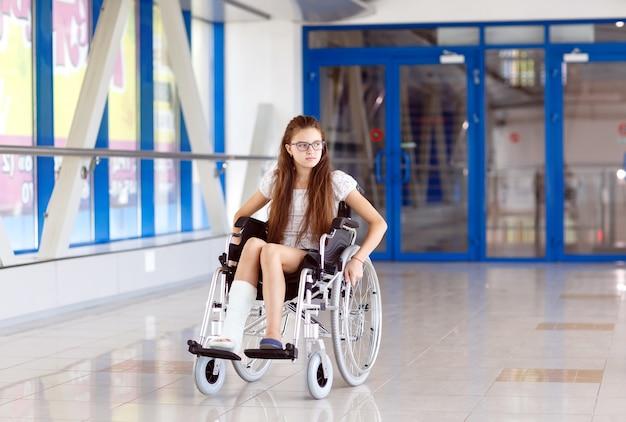 Een jong meisje in een rolstoel staat in de gang van het ziekenhuis.