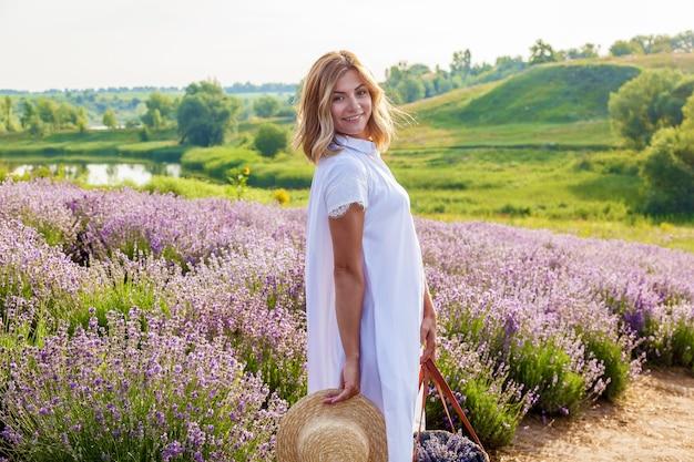 Een jong meisje in een witte jurk en een mand loopt in de vroege ochtend door het lavendelveld