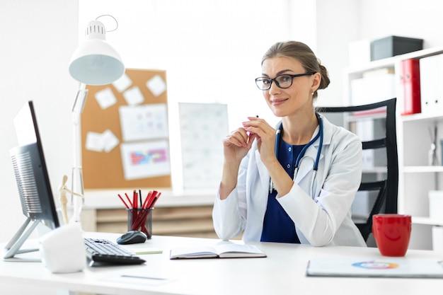 Een jong meisje in een witte mantel zit aan de tafels op kantoor en houdt een pen in haar hand.