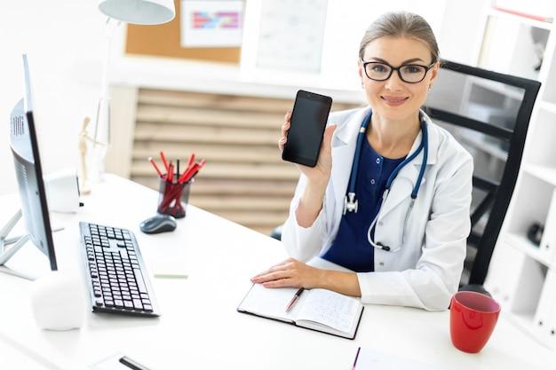 Een jong meisje in een witte mantel zit aan een tafel op kantoor en heeft een telefoon in haar hand. een stethoscoop hangt om haar nek.