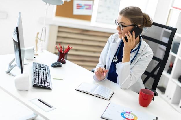 Een jong meisje in een witte robe zit aan de balie op kantoor, aan de telefoon te praten en een pen vast te houden