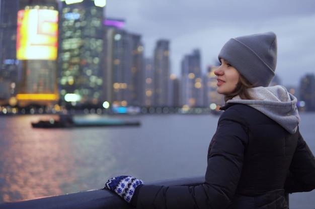 Een jong meisje in een zwart jasje en hoed kijkt naar de bezienswaardigheden van shanghai aan de waterkant van de vaitan