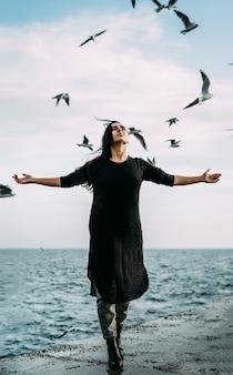 Een jong meisje in een zwarte jurk en spijkerbroek staat aan zee met een sterke wind.