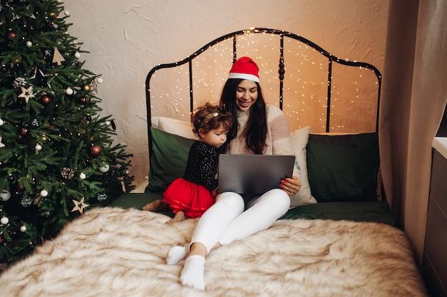 Een jong meisje in oudejaarskleren kijkt naar een tv-serie op het bed met een kind