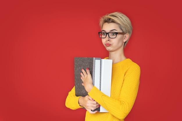 Een jong meisje is verbaasd over het werk, heeft mappen met documenten bij zich en denkt aan werk.