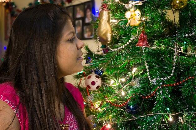 Een jong meisje kijkt naar de versieringen op de kerstboom