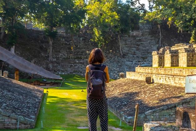 Een jong meisje kijkt naar het balspelveld in de tempels van copan ruinas. honduras