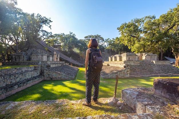 Een jong meisje kijkt naar het balspelveld in de tempels van copan ruinas