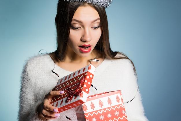 Een jong meisje kreeg een cadeau voor het nieuwe jaar en kijkt verrast