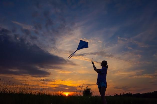 Een jong meisje lanceert een vlieger in de lucht. silhouet tegen de zonsondergang