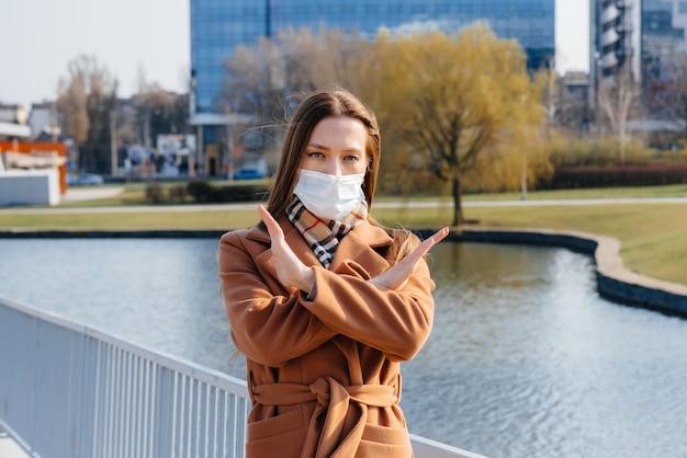 Een jong meisje loopt in een masker tijdens de pandemie en het coronovirus. quarantaine.