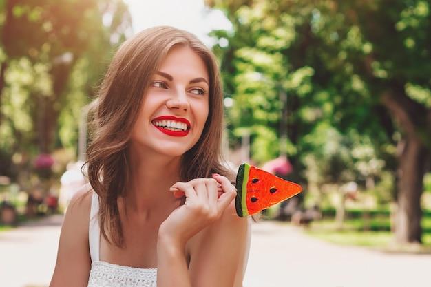 Een jong meisje loopt in het park met een lolly in de vorm van watermeloen. meisje dat in strohoed in het park glimlacht