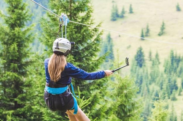 Een jong meisje maakt een foto van zichzelf op een mobiel terwijl ze afdaalt op een kabelbaan