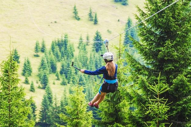 Een jong meisje maakt een foto van zichzelf op een mobiel terwijl ze afdaalt op een zipline