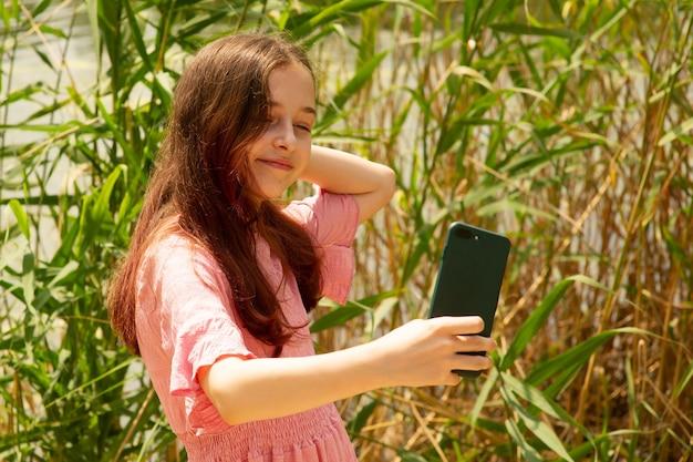Een jong meisje maakt een selfie. de tiener spreekt via video. technologieconcept.