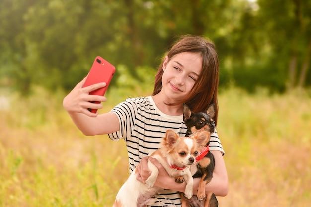 Een jong meisje maakt een selfie op een smartphone met honden in de natuur. tiener en dieren.