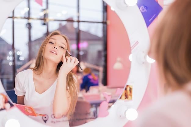 Een jong meisje maakt make-up in een schoonheidssalon. het meisje voor de spiegel is aan het verzinnen. schoonheidssalon