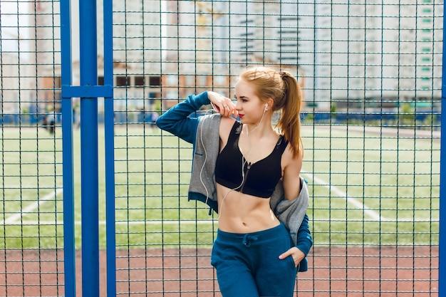 Een jong meisje met een aantrekkelijk figuur staat in de buurt van een blauw hek op het stadion. ze draagt een blauw sportpak met een zwarte top. ze luistert naar de muziek met een koptelefoon en kijkt ver weg.