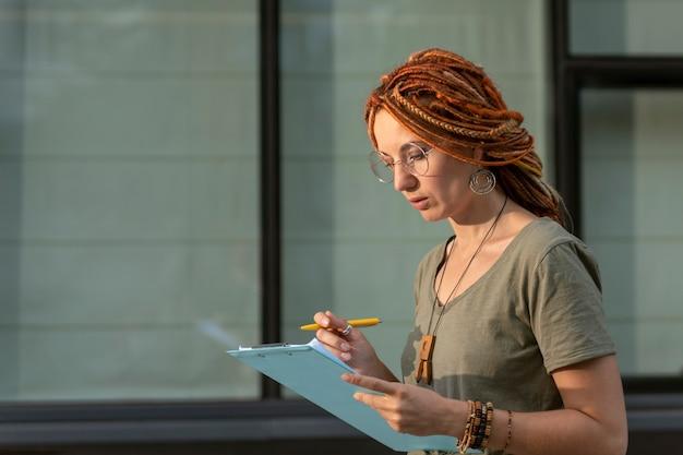 Een jong meisje met een afwijkend uiterlijk leest informatie op een tablet. student doet sociaal onderzoek onder de bevolking