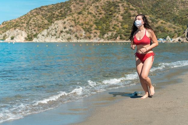 Een jong meisje met een beschermend masker en rode strandkleding op het strand rennen
