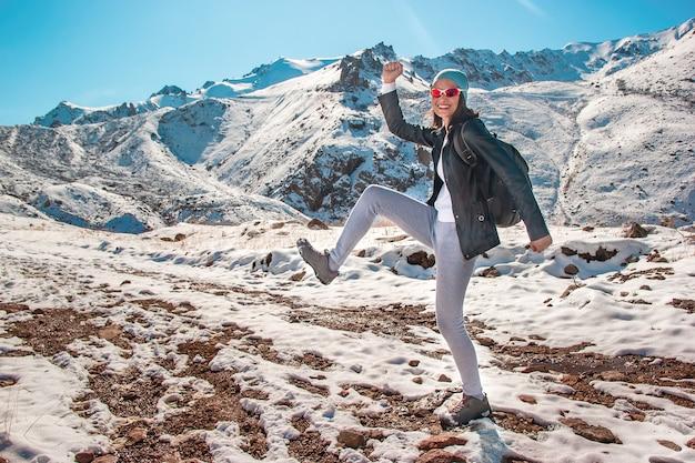 Een jong meisje met een bril danst in de sneeuw. bergtoppen in het winterseizoen.