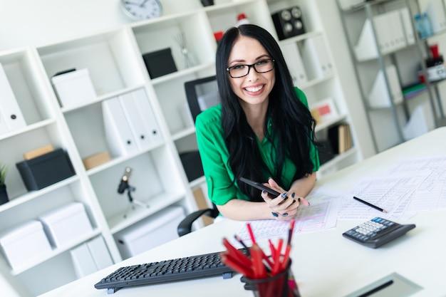 Een jong meisje met een bril op kantoor houdt een telefoon in haar handen en glimlacht