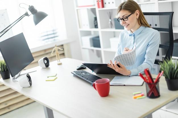 Een jong meisje met een bril zit aan een tafel op kantoor, houdt een potlood in haar hand en werkt met documenten.
