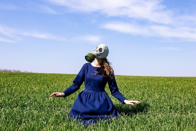 Een jong meisje met een gasmasker staat in een groen veld. pandemie. coronavirus.