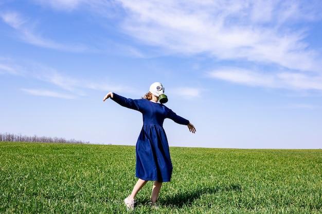 Een jong meisje met een gasmasker staat in een groen veld
