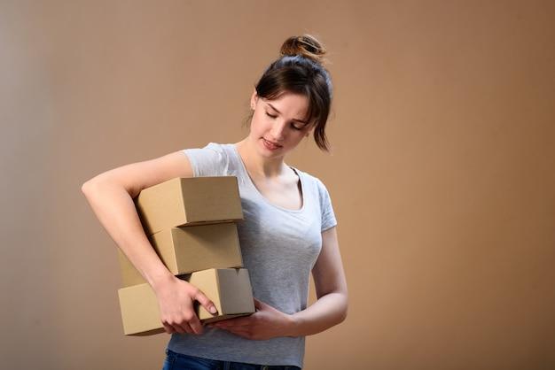 Een jong meisje met een glimlach kijkt naar de dozen die ze in haar handen op een beige ruimte houdt.