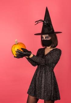 Een jong meisje met een heksenhoed houdt een pompoen vast