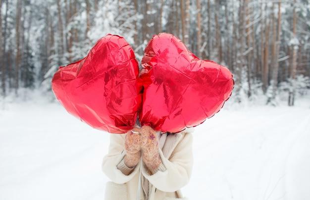Een jong meisje met een heldere hartvormige ballon staat in een besneeuwd bos. valentijnsdag. voor de wintervakantie.
