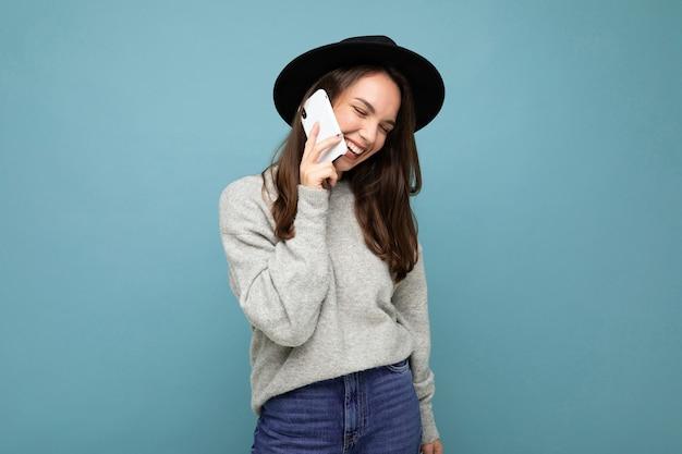 Een jong meisje met een hoed spreekt aan de telefoon