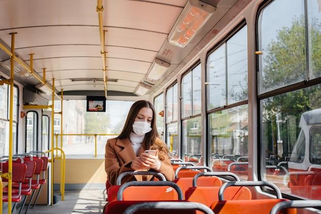 Een jong meisje met een masker gebruikt alleen het openbaar vervoer tijdens een pandemie. bescherming en preventie covid 19.