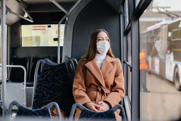 Een jong meisje met een masker gebruikt alleen het openbaar vervoer tijdens een pandemie