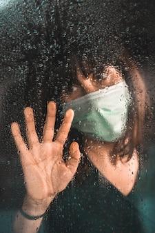 Een jong meisje met een masker in de covid-19 pandemie kijkt uit het raam op een regenachtige dag