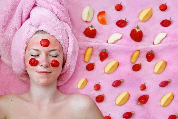 Een jong meisje met een roze handdoek ligt met haar ogen dicht met een aardbeimasker op haar gezicht. stukjes fruit in de buurt.