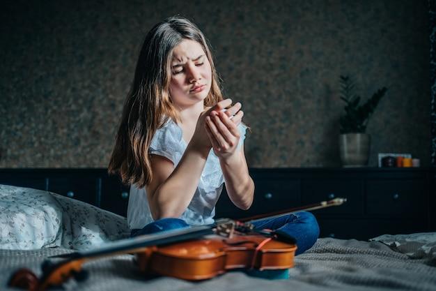 Een jong meisje met een viool zit op het bed en houdt met haar hand een gewonde vinger vast