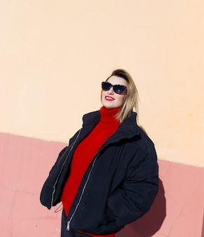Een jong meisje met een zonnebril, een zwart jasje en een rode trui poseert tegen een muur. hard licht