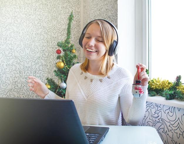 Een jong meisje met koptelefoon communiceert op afstand met behulp van een computer