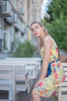 Een jong meisje met lange witte krullen in een jurk poseren in de oude stad in de zomer. meisje