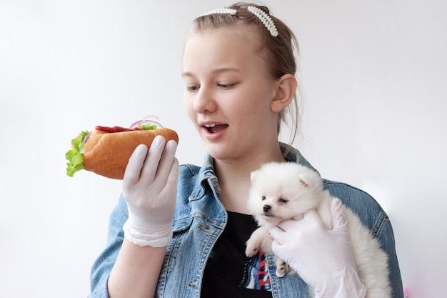Een jong meisje met licht haar in een blauw spijkerjasje en medische handschoenen houdt een hotdog in de ene hand en een kleine witte pommerse hond in de andere..