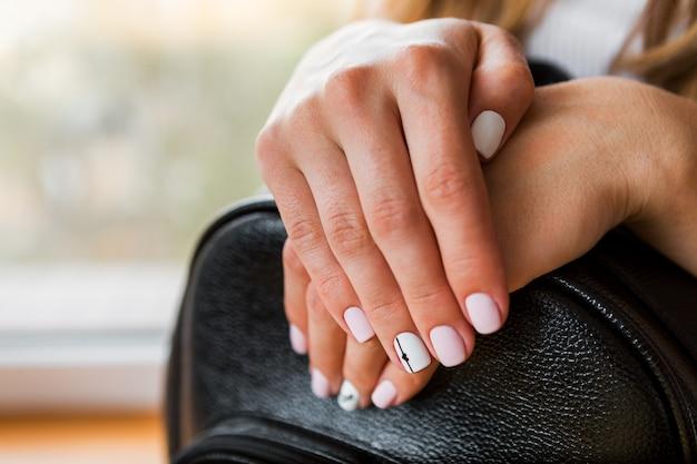 Een jong meisje met mooie witte manicure houdt een zwarte aktentas. stijl van mode
