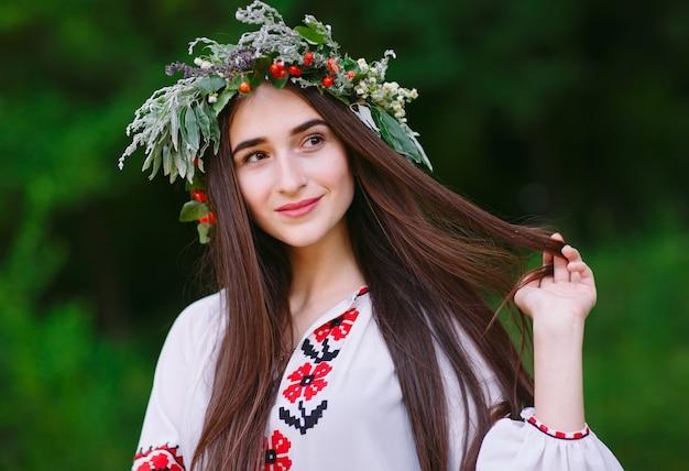 Een jong meisje met slavische uitstraling met een krans van wilde bloemen op de midzomer.